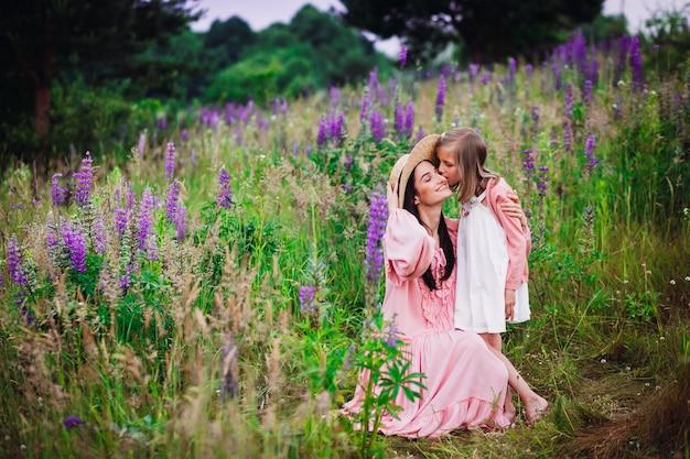 Vrouw en meisje in roze jurken poseren op het gebied van lavendel
