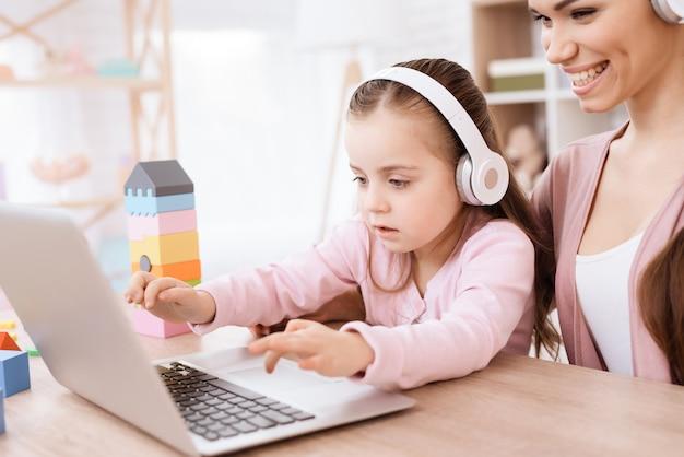 Vrouw en meisje kijken samen naar het laptopscherm.