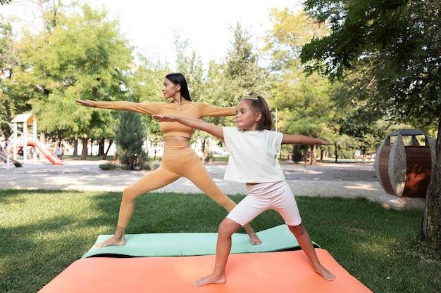 Vrouw en meisje mediteren buitenshuis full shot