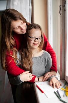 Vrouw en meisje met het syndroom van down poseren door raam