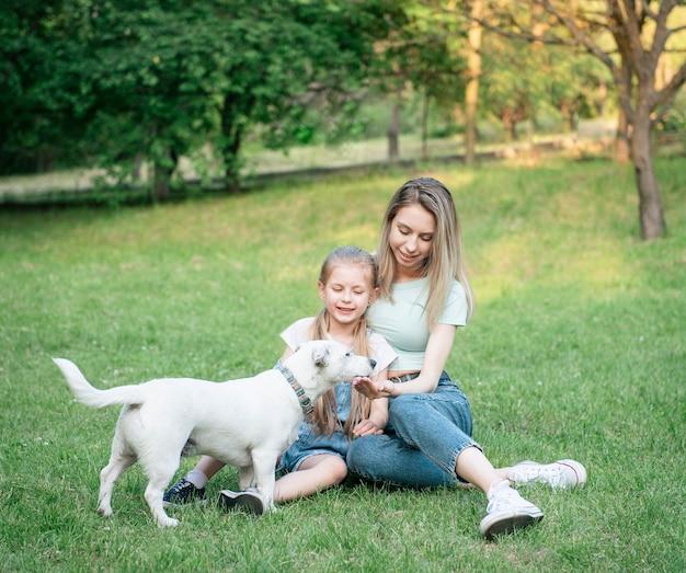 Vrouw en meisje spelen met een hondenras jack russell terrier