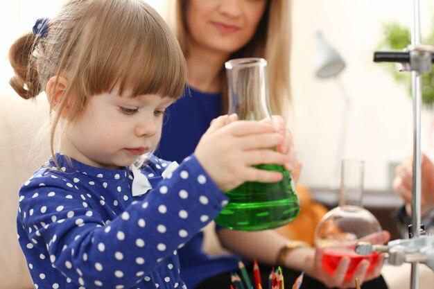 Vrouw en meisje spelen met kleurrijke vloeistoffen