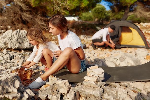 Vrouw en meisje wat betreft grote steen bij strand.