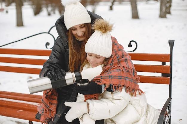 Vrouw en meisje, zittend op een bankje