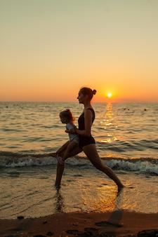 Vrouw en meisjessilhouet die in evenwicht brengende yoga uitoefenen