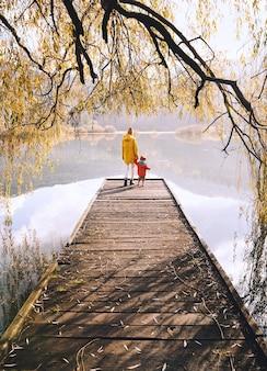 Vrouw en peuter op houten pierbrug in de buurt van meer omringd door takken van wilgenboom in de herfst
