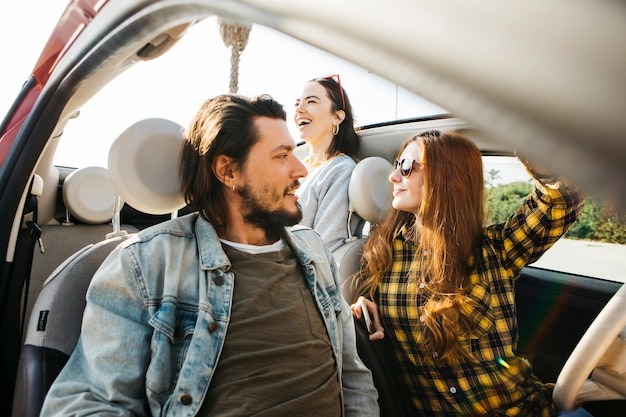 Vrouw en positieve man zit in de auto in de buurt van glimlachende dame leunend uit auto