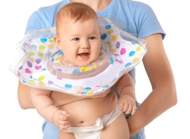 Vrouw en schattige baby met opblaasbare ring op wit