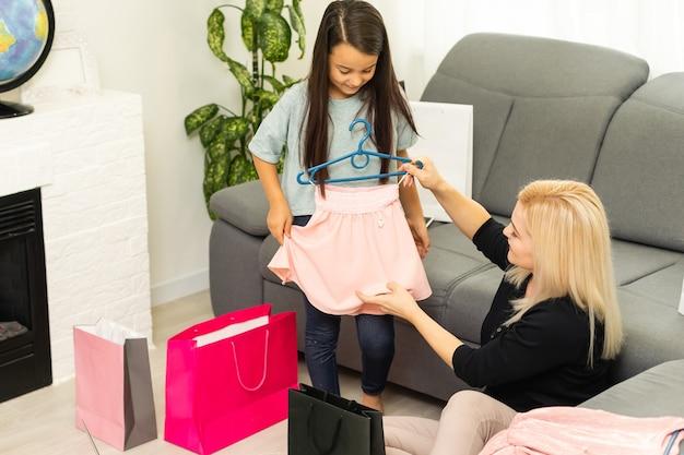 Vrouw en schattige dochter met geschenken thuis. moeder en dochter met boodschappentassen en pakjes. gelukkig familie en winkelconcept. familie met lachende gezichten openen cadeautjes thuis. zwarte vrijdag