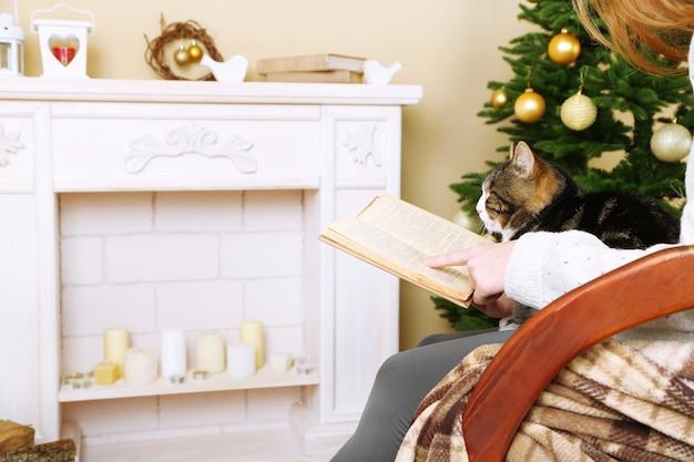 Vrouw en schattige kat zitten op schommelstoel en lezen het boek voor de open haard