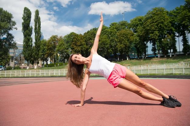 Vrouw en sporten. sexy jonge sportvrouw genieten van sportactiviteiten op zomerdag. atletische vrouw in sportkleding training op stadion. sport, fitness en gezondheid.