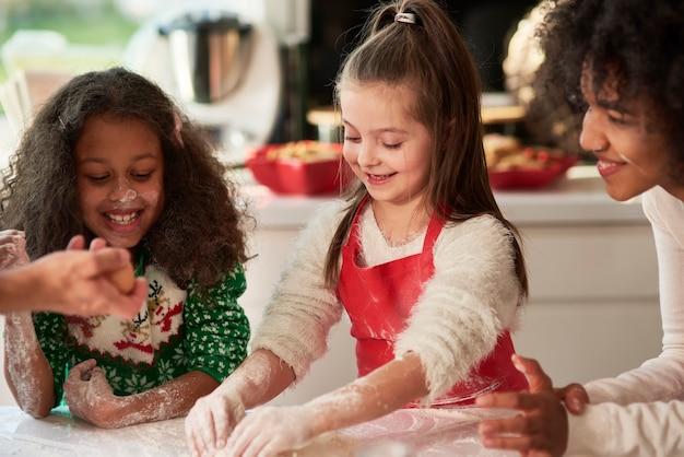 Vrouw en twee meisjes die kerstkoekjes voorbereiden