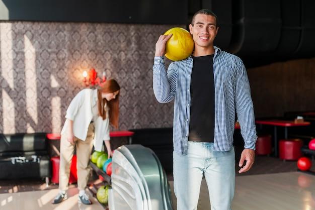 Vrouw en vrouw met bowlingballen in een bowlingclub