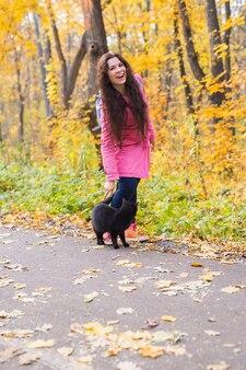 Vrouw en zwarte kat lopen in de herfstpark