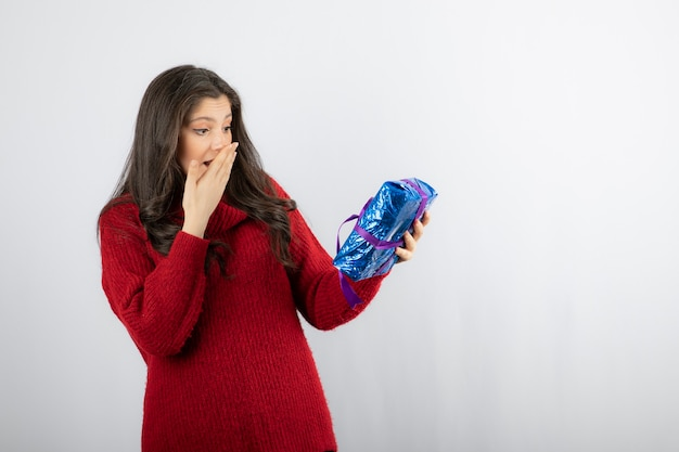 Vrouw enthousiast over een kerstcadeaudoos met paars lint.