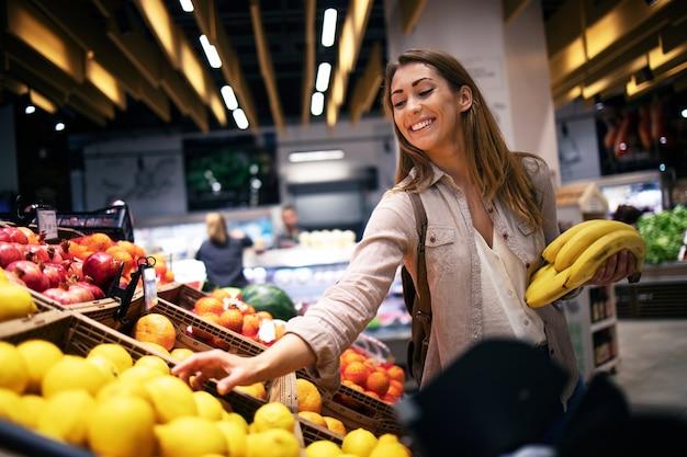 Vrouw eten bij de supermarkt-supermarkt kopen
