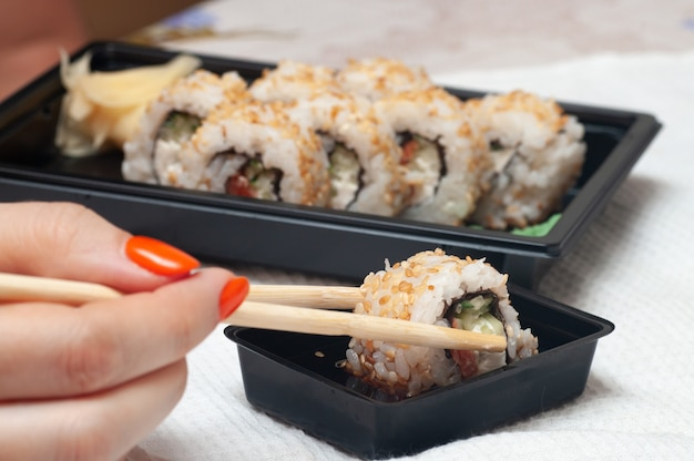 Vrouw eten thuis afgeleverd sushi.