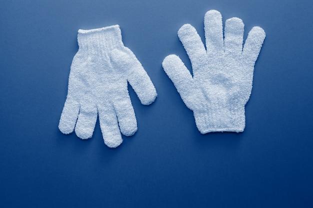 Vrouw exfoliërende handschoenen voor gebruik onder de douche voor massage en scrub afgezwakt in trendy klassieke blauwe kleur van het jaar 2020.