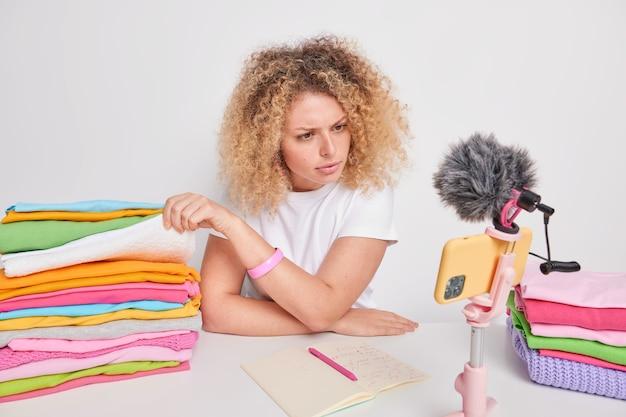 Vrouw expert in machine wassen scheidt kleding op materiaal en kleur legt uit van welke stof het is gemaakt neemt video op voor internetabonnees geeft advies hoe de juiste wascyclus te kiezen
