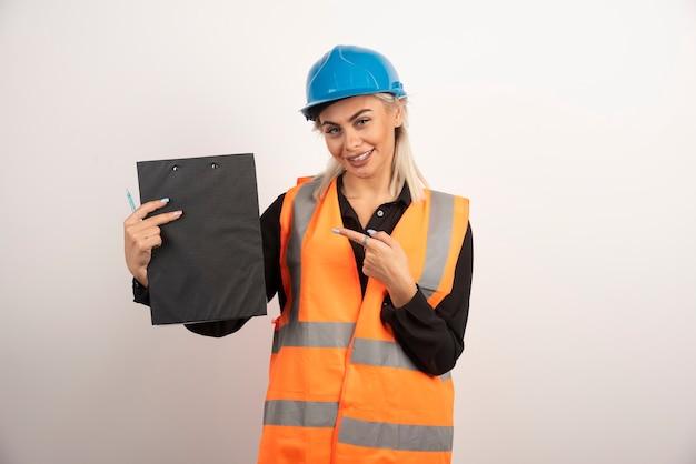 Vrouw fabrieksarbeider wijzend op klembord op witte achtergrond. hoge kwaliteit foto