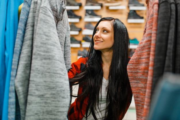 Vrouw fietsen jas kiezen, winkelen in sportwinkel.