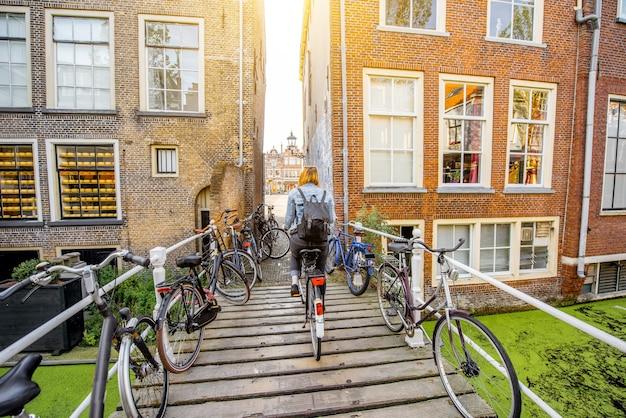 Vrouw fietsen op de brug in de stad delft tijdens het ochtendlicht, nederland