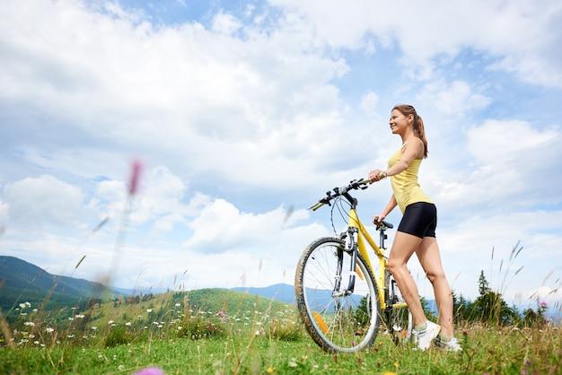 Vrouw fietser op met gras begroeide heuvel