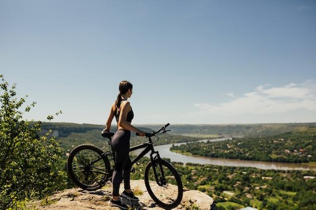 Vrouw fietser permanent met fiets op rots op berg