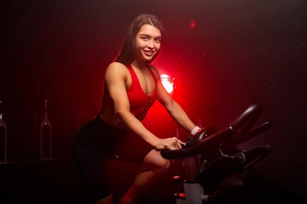 Vrouw fietser, zit op de fiets en glimlach naar de camera, geniet van training. ze traint in de sportschool, fietst op de trainer