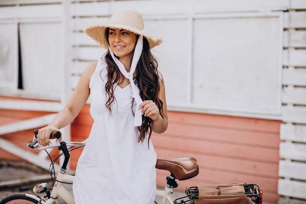 Vrouw fietsten in jurk en hoed