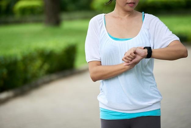 Vrouw fitness armband controleren