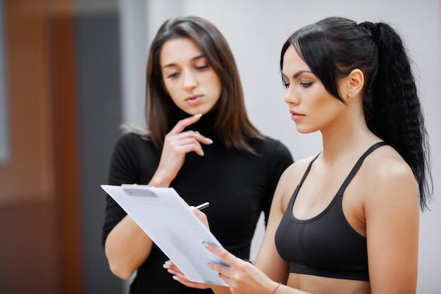 Vrouw fitness coach schrijft een trainingsprogramma voor de fitnessclub van de klant