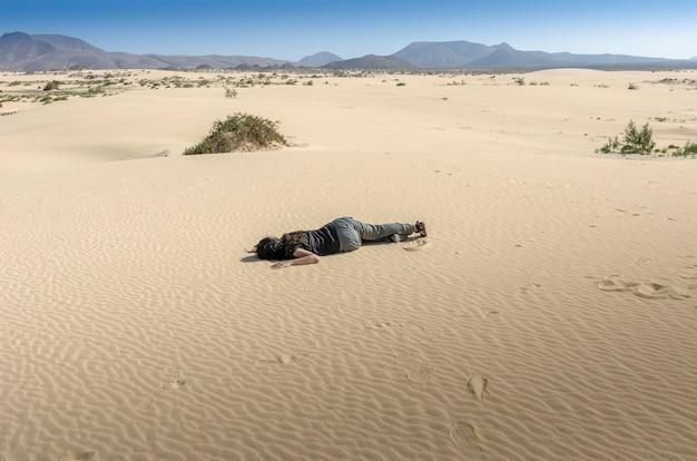 Vrouw flauwgevallen in het midden van het woestijnzand. ze is uitgedroogd en verdwaald. eiland fuerteventura.