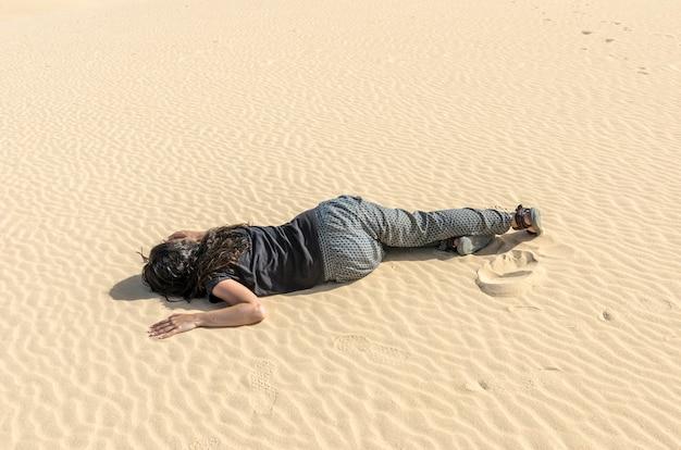 Vrouw flauwgevallen in het midden van het woestijnzand. ze is uitgedroogd en verdwaald.