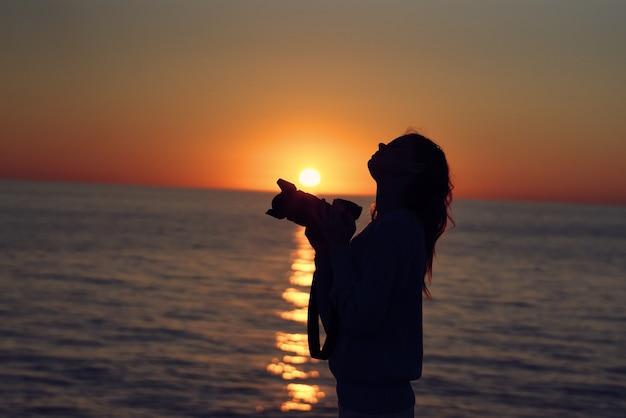 Vrouw fotograaf buitenshuis zonsondergang frisse lucht landschap. hoge kwaliteit foto