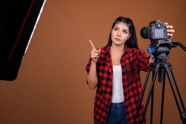 Vrouw fotograaf camera op statief aanpassen tijdens het denken