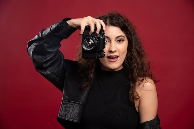 Vrouw fotograaf in alle zwarte outfit fotograferen met een camera.