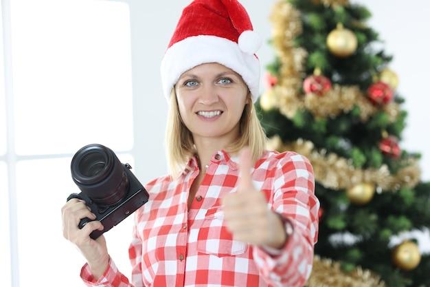 Vrouw fotograaf in kerstman hoed op achtergrond van kerstboom maakt duimen omhoog gebaar