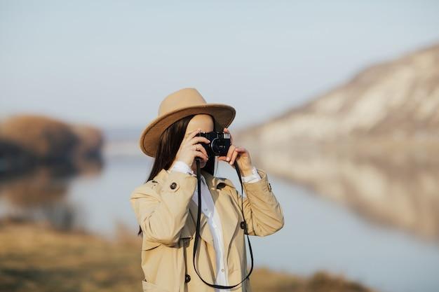 Vrouw fotograaf in trenchcoat en hoed foto nemen op vintage filmcamera