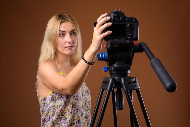 Vrouw fotograaf met dslr camera op statief in studio