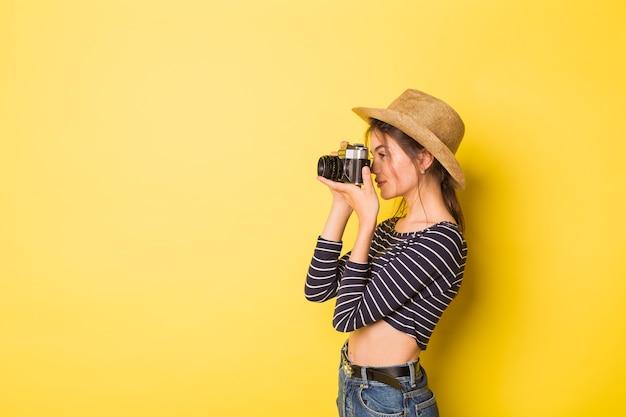 Vrouw fotograaf schoonheid kaukasisch brunette jong meisje op gele achtergrond