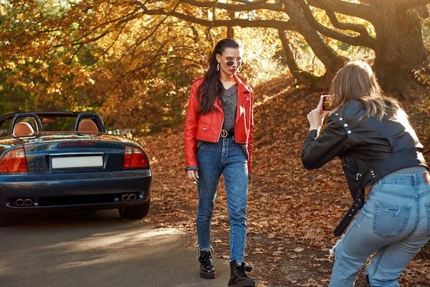 Vrouw fotografeert haar vriend in rode jas en zonnebril in de buurt van cabriolet