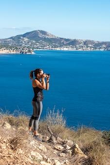 Vrouw fotografeert met haar camera naar het landschap, in de natuur vanaf de peñon de ifach in calpe