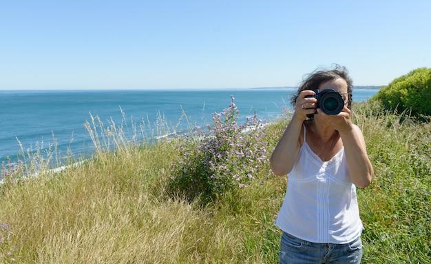 Vrouw fotograferen met camera aan de zee