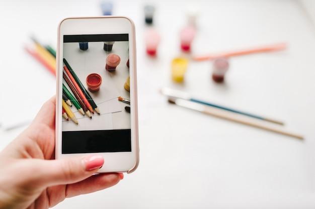 Vrouw fotograferen met mobiele smartphone camera werkruimte van kunstenaar voor het tekenen van kleurpotloden, aquarel, verf, penseel, schetsboek, papier geïsoleerd op een wit oppervlak