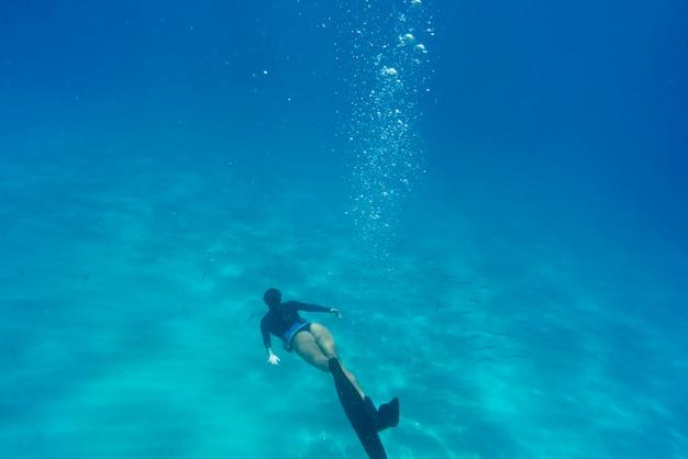 Vrouw freediving met zwemvliezen onder water
