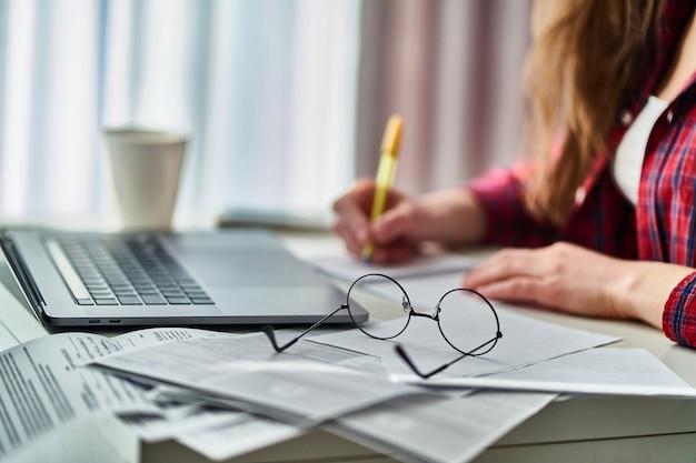 Vrouw freelancer die op afstand aan laptop werkt en belangrijke gegevensinformatie in notitieboekje neerschrijft.
