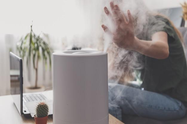 Vrouw freelancer gebruikt een huishoudelijke luchtbevochtiger op de werkplek om de relatieve vochtigheid en het microklimaat op de werkplek van het thuiskantoor te behouden met een laptop en documenten.