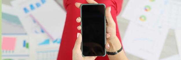 Vrouw freelancer houdt smartphone in handen op vloerdocumenten met zakelijke grafieken met statistieken