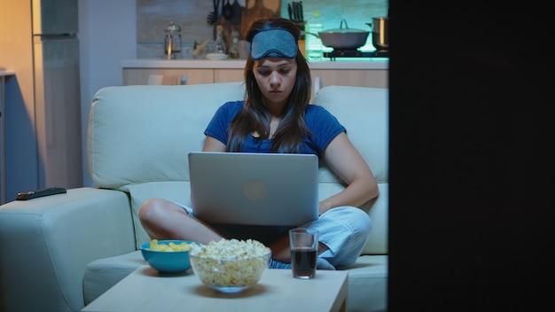 Vrouw freelancer in pijamas die 's avonds laat op laptop voor tv werkt. gelukkig persoon in pijamas met oogmasker zittend op de bank lezend schrijven zoekend browsen op notebook met behulp van internettechnologie